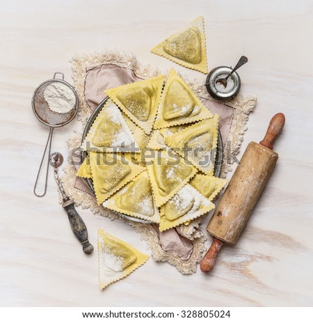 ravioli  Triangoli making set, preparation on white wooden background, top view. Italian food concept. - stock photo
