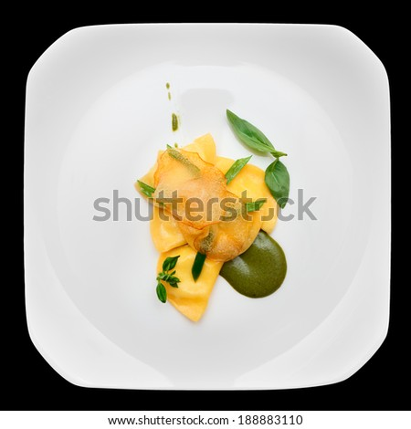 Ravioli with pesto sauce and potato chips in plate, isolated on black - stock photo