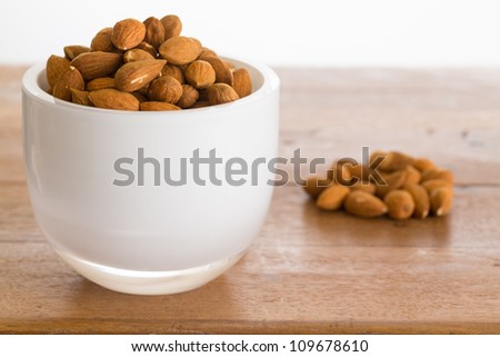 Raw almond nuts in white glass bowl on old wooden table - stock photo