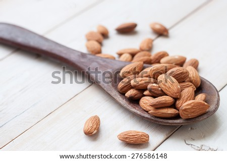Raw almonds on white wooden board - stock photo