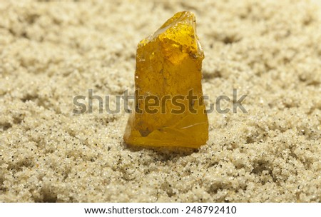 Raw amber from the shores of the Baltic Sea in the Kaliningrad region , lying on the sand - stock photo