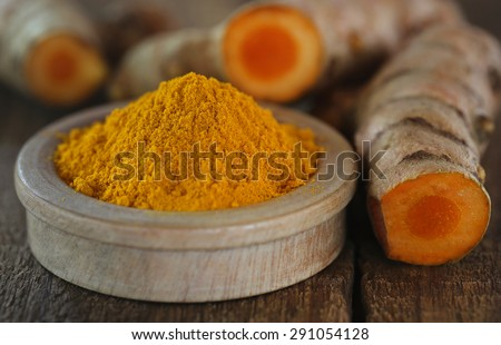 Raw and ground turmeric on wooden surface - stock photo