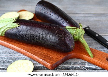 Raw aubergines on a cutting board, fresh vegetable - stock photo