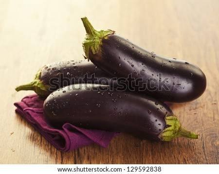 Raw aubergines or eggplants on wooden backround. - stock photo