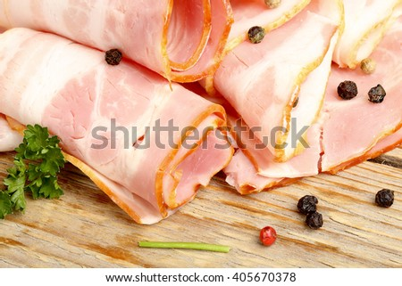 raw bacon slices with parsley and pepper  - stock photo