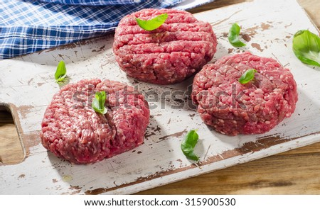 Raw beef burger patties on  wooden cutting board. Selective focus - stock photo