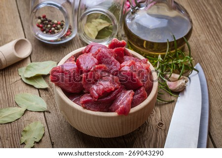 Raw beef diced in a wooden bowl. - stock photo