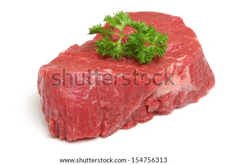 Raw beef fillet steak with sprig of parsley.