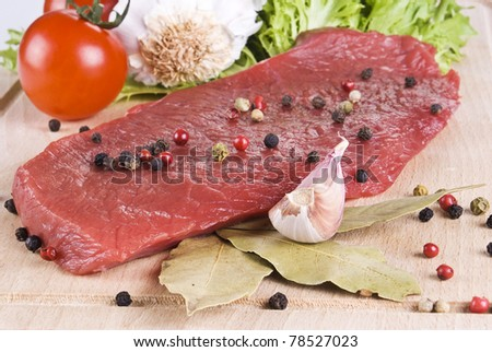 Raw beef frying steak on chopping board with vegetables - stock photo