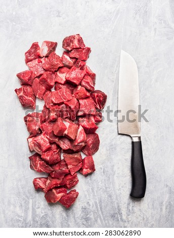 Raw beef goulash meat diced for stew with meat knife on light gray wooden background, top view - stock photo
