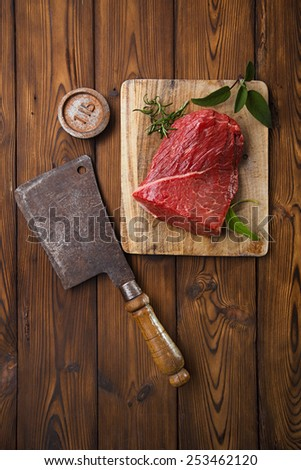 raw beef meat fillet  on wooden  table with meat cleaver and 1lb iron weight - stock photo