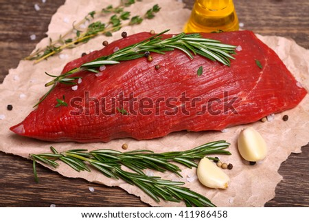 Raw beef meat with rosemary, garlic and spices on a wooden background - stock photo