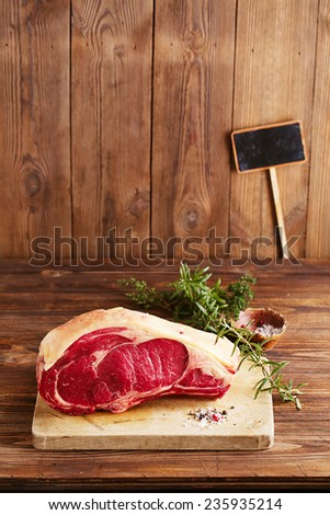 raw beef Rib bone  steak   on wooden board and table with empty black sign - stock photo