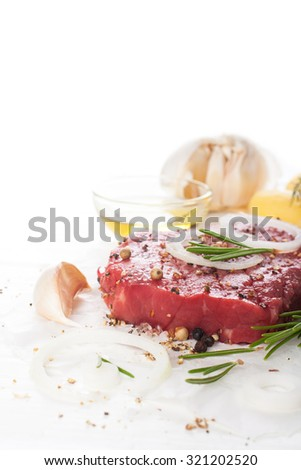 Raw beef steak and spices over white.  Healthy food concept with copy space for text. Selective focus. - stock photo