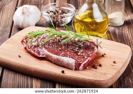 Raw beef steak on a cutting board - stock photo