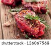 Raw beef steak on a dark wooden table. - stock photo