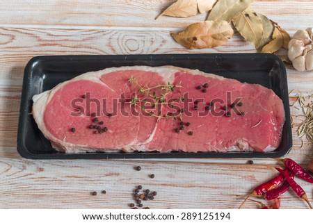 Raw beef steak on wood - stock photo