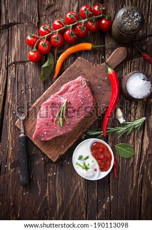 Raw beef steak on wooden table, close-up - stock photo
