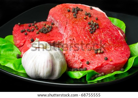 Raw beef steak with garlic and black pepper on black plate - stock photo