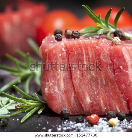 Raw beef steak with peppercorns and herbs.