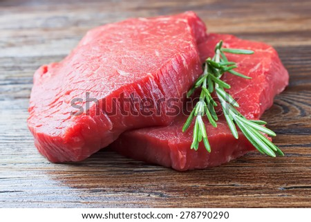 raw beef steak with rosemary on brown wooden background - stock photo