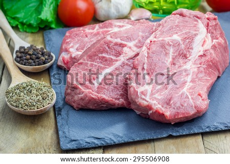 Raw beef steak with seasoning on a black slate tray - stock photo