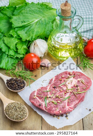 Raw beef steak with seasoning on a parchment paper - stock photo