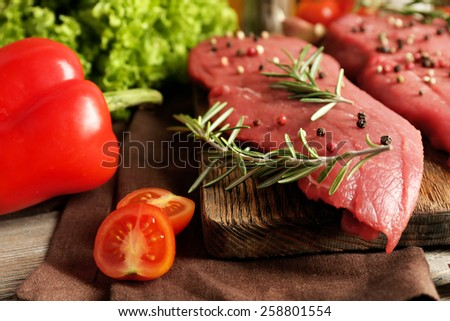 Raw beef steak with spices and greens on table close up - stock photo