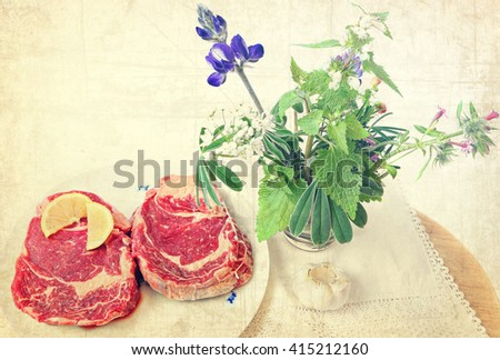 Raw beef steak with spices (sliced lemon and garlic) ready for cooking. Wild herbs and flowers on the wood board. Food ingredients and herbs still life. Old paper texture. Vintage image - stock photo