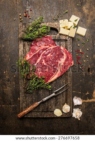Raw beef steak with thyme,butter and meat fork on dark rustic cutting board, top view - stock photo