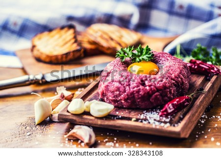 Raw beef .Tasty Steak tartare. Classic steak tartare on wooden board. Ingredients: Raw beef meat salt pepper egg garlic chili herb decoration and toast bread  - stock photo
