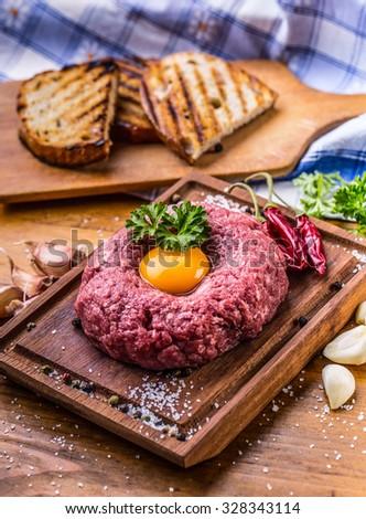 Raw beef .Tasty Steak tartare. Classic steak tartare on wooden board. Ingredients: Raw beef meat salt pepper egg garlic chili herb decoration and toast bread  - stock photo