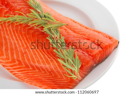 raw big salmon bar on white plate and rosemary
