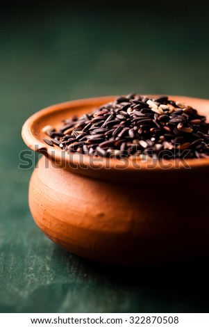 raw black glutinous rice in earthen pot against dark background - stock photo