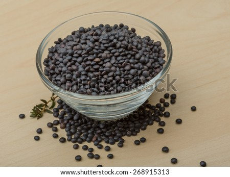 Raw Black lentils on the wood background