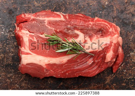 Raw blade roast with rosemary on brown rustic background - stock photo