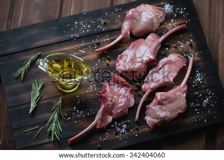 Raw bobby veal rack steaks on a rustic wooden chopping board, high angle view - stock photo