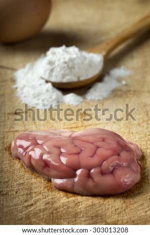 Raw brain on wood preparation for cooking with egg and flour - stock photo