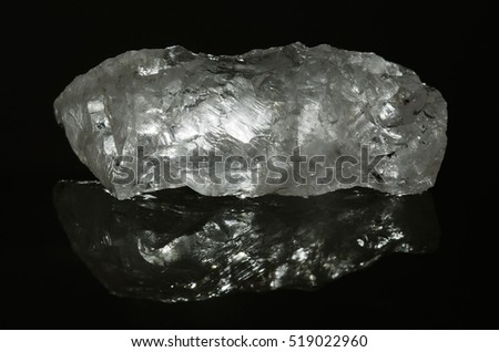 Raw brit stone of quartz crystal on an horizontal position over a reflexive surface on a dark background set and with a back light shining through. Semi-clear transparent crystal.