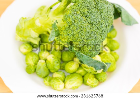 Raw broccoli and brussels sprout in a white plate on the kitchen table washed and ready for cooking - stock photo
