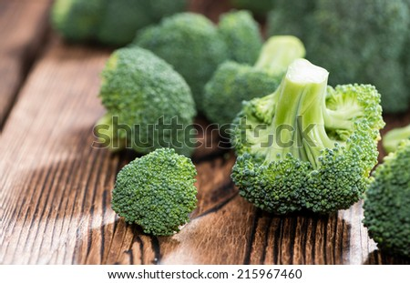 Raw Broccoli (detailed close-up shot) on wooden background - stock photo