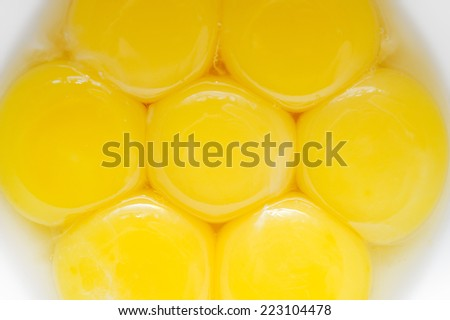 Raw broken eggs in a bowl. The yolk together with becomesthe large planeman these eggs to use in cooking - stock photo