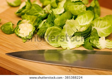 Raw Brussels sprouts on a cutting board with a knife