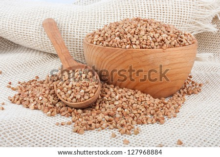 Raw buckwheat in wooden bowl and spoon on burlap, food ingredient photo