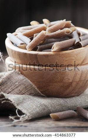 Raw buckwheat pasta on the wooden table, selective focus