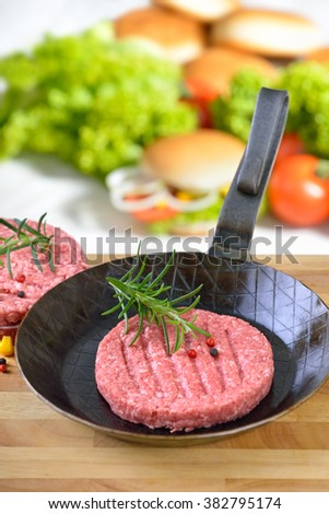 Raw burger patty in an iron pan ready to fry, some burger ingredients in the background - stock photo