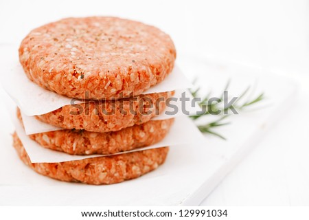Raw burgers for hamburgers, in a pile - stock photo