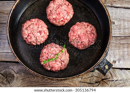 raw burgers from organic beef in a frying pan on an old wooden table - stock photo