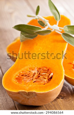 Raw butternut squash halved with sage on wooden table - stock photo