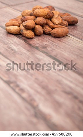 Raw cacao beans over wooden background